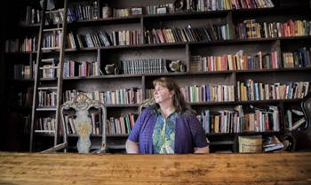 Elaine Calloway sitting at desk with library shelves of books behind her as the backdrop.